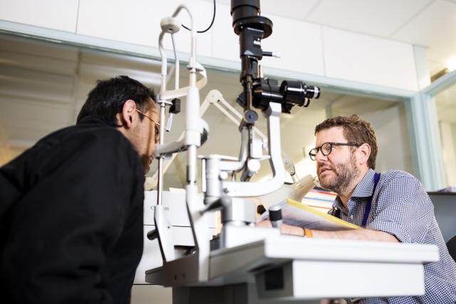 Professor Gazzard performs eye treatment on patient